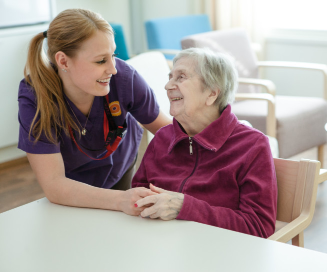 Nurse and elderly woman at the table.
