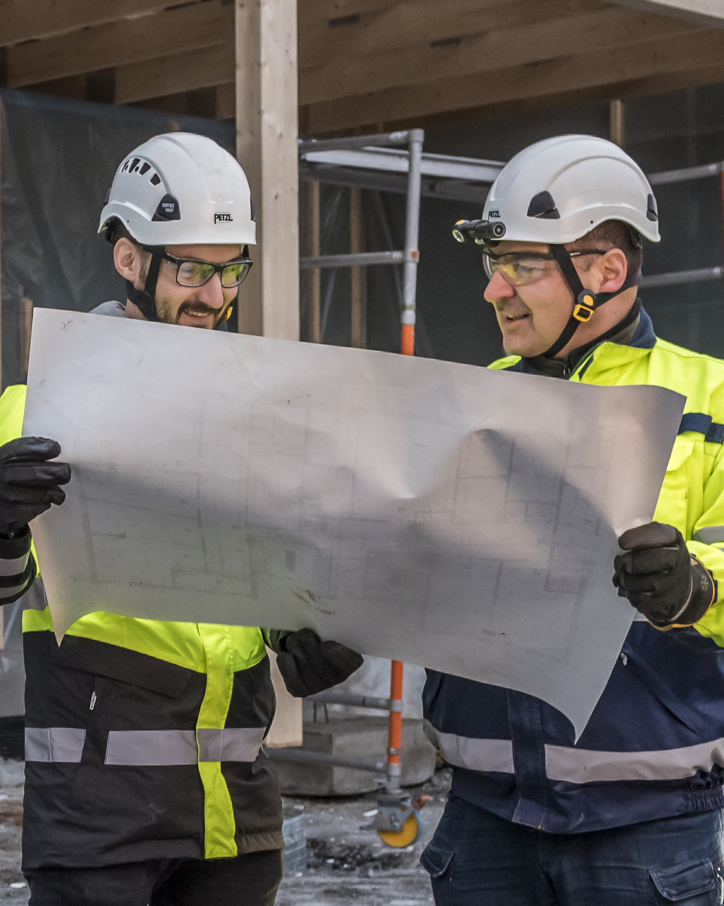 Two men in work clothes are reading a plan at a construction site.